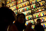 "Patrons having drinks at Bretton bar in Athens. The unsuspected visitor of the historic center of Athens cannot miss the hundreds of colorful bottles and lights that decorate the walls of ""Brettos"".  ""BRETTOS"" is the oldest distillery in Athens. It started operating for the first time back in 1909 at the ground level of an Athenian old mansion in the heart of Plaka. At those premises, his founder, Michael Brettos, started producing ouzo, brandy and few liqueur flavours. It is the 2nd oldest distillery in Europe. Athens is the capital and largest city of Greece. It dominates the Attica periphery and is one of the world's oldest cities, as its recorded history spans around 3,400 years. Classical Athens was a powerful city-state. A centre for the arts, learning and philosophy."