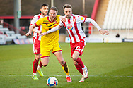 Stuart Sinclair of Walsall about to be tackled from the front by Femi Akinwande of Stevenage during the EFL Sky Bet League 2 match between Stevenage and Walsall at the Lamex Stadium, Stevenage, England on 20 February 2021.