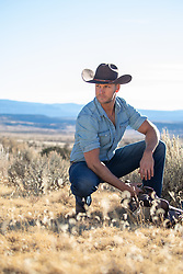 cowboy kneeling down on a rustic mountain view ranch