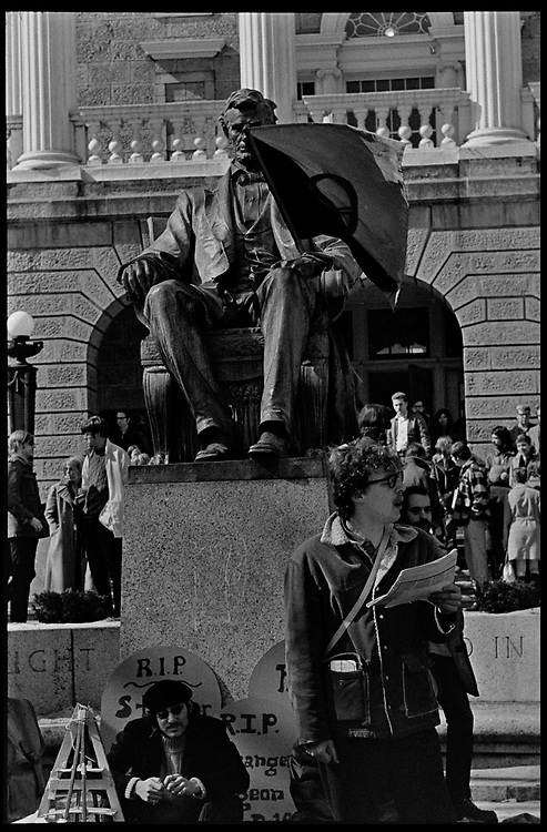 Madison, WI - March 1970. A student speaks near the statue of Abraham Lincoln in front of Bascom Hall, the statue with a black and red anarcho-syndicalism flag. On March 15, 1970, the University of Wisconsin - Madison Teaching Assistants' Association voted to strike, and the campus was filled with picket lines as well as demonstrations of related and other issues. The strike lasted until early April, when the Association and University came to an agreement.