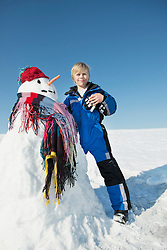 Boy standing with snowman, Bavaria, Germany