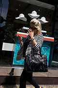 Woman walks past a sunglasses shop featuring three hats suspended from the store window ceiling. The lady consumer passes the dark window selling summer eyewear in London's Long Acre, a street near the capital's Covent Garden, Westminster. Looking at her smartphone while walking along the street, the woman wears a striped top and carries a large, shiny handbag held in the crook of her elbow. The three white hats that symbolise a London summer, hanging in clear space above the woman's head.