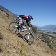 Scott McGregor from Tepuke in action during the New Zealand South Island Downhill Cup Mountain Bike series held on The Remarkables face with a stunning backdrop of the Wakatipu Basin. 150 riders took part in the two day event. Queenstown, Otago, New Zealand. 9th January 2012. Photo Tim Clayton