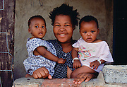 A smiling  mother holds her two children in the township of Soweto, South Africa