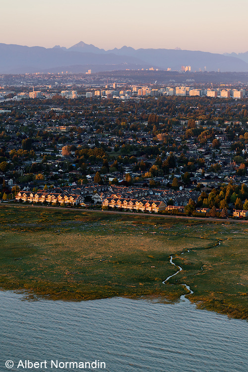 Aerial view of city and distant mountains, Richmond, BC, Canada