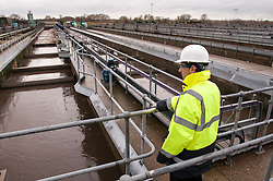 Inspector checks an aeration tank on sewage works. Aeration encourages micro-organisms to feed on bacteria in the processed sewage (secondary treatment).