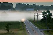 A car drives through low lying fog on a rural road near St Anna, Wisconsin