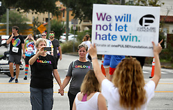 June 10, 2017 - Orlando, FL, USA - Pulse nightclub owner Barbara Poma holds up a sign for runners passing her club during the CommUNITYRainbowRun 4.9K road race on Saturday, June 10, 2017, in Orlando, Fla. The race is one of many events across central Florida commemorating the one-year anniversary of the June 12, 2016, massacre that killed 49 at Pulse. (Credit Image: © Joe Burbank/TNS via ZUMA Wire)