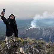 A member of the tourist police, a group that helps escort tourists to sites of special interest in Guatemala, poses for a selfie with the Santiaguito lava dome complex in Guatemala.