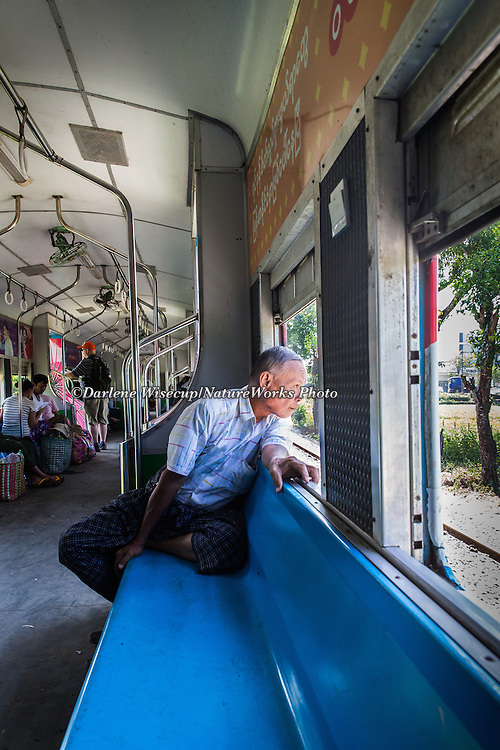 A passenger observes the sights as they pass by on the Yangon Circle Line Train.  Yangon, Myanmar.