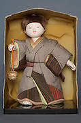 Japanese male doll holding a bell in a box
