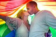 A couple in love kiss under the light of a rainbow flag.