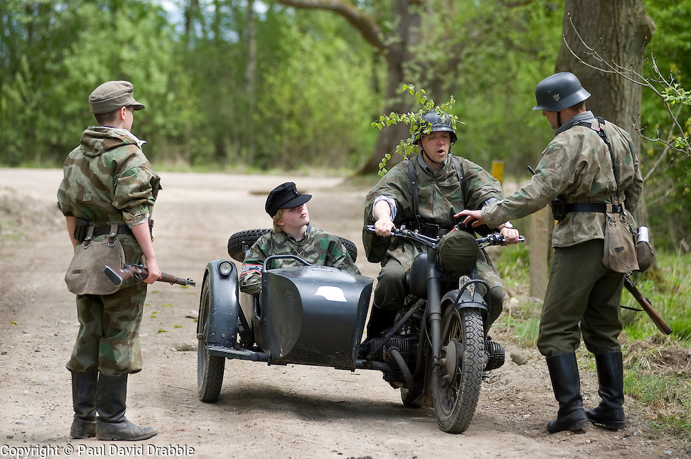 Reenactors from Northern World War Two Association, portraying elements of the elite Grossdeutschland division with a motorcycle and sidecar combinatione take part in a 24hr private exercise, held at Sutton Grange, near Ripon in Yorkshire. The white steel helmet or Stahlhelm marked on the front of the sidecar is the Großdeutschland Division tactical symbol, <br /> 15  May 2010 <br /> Images © Paul David Drabble.