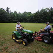 7/3/11 -- Rt 129 , Maine. Jim and Nancy Bailey chat for a bit while finishing up the grass for the day. ...A stretch of the road not often traveled. Spanning communities, classes and styles ~ of farmers and fishermen, retired and plugging, the elite and working waterfront. (This area has huge potential for great photojournalism).  Photo by Roger S. Duncan.