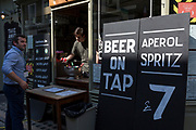 A customer orders a cold drink from a re-opened bar in Soho where beer on tap is available on the day that UK Prime Minster, Boris Johnson announced in parliament a major easing of Coronavirus pandemic restrictions on July 4th next week, including the re-opening of pubs, restaurants, hotels and hairdressers in England, on 23rd June 2020, in London, England. The three month two metre social distance will be also reduced to one metre plus but in the last 24hrs, a further 171 have died from Covid, bringing the UK total to 42,927.