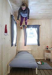 An employee in the bedroom of the 'The Upside Down House', a zero-gravity illusion experience, in The Triangle in Bournemouth, Dorset.