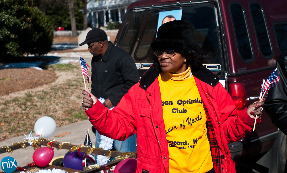 Wilma Means hands out American flags prior to the Martin Luther King Day Parade down Union Street in Concord Saturday afternoon. (Photo by James Nix)
