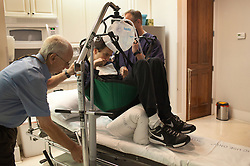 Dr. Eddie Zant and his assistant move Chris Cox, 29, onto a stretcher to receive hyperbaric oxygen therapy, Destin, Fla., Nov. 18, 2011. Cox was left with debilitating back pain after an A.T.V. accident. He underwent physical therapy to no avail and accidentally overdosed on Oxycontin, leaving him clinically deceased for 15 to 30 minutes. He was revived but suffered severe lack of oxygen to his brain and was diagnosed as minimally conscious. Cox's family entered him into a clinical trial, testing medicines that evoked Òparadoxical excitation,Ó such as Ambien, and have witnessed a heightened sense of awareness in their son.