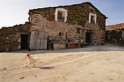 A cock strolls through the remote picturesque village of Santa Marina, which has a crackerbox church and stone roofs. There is no permanent priest in the town. However whenever a priest visits, there are masses. The town has electricity but there just as easily could not be. The town has few inhabitants. Rioja, Spain.