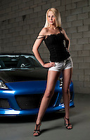 Sensual blond girl stading in front of sport car in a garage.