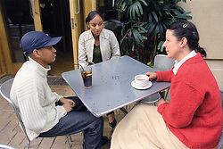 Single mother sitting at table outside cafe with teenage daughter and son,