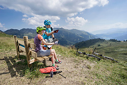 Young couple of mountainbikers looking at map in alpine landscape, Zillertal, Tyrol, Austria