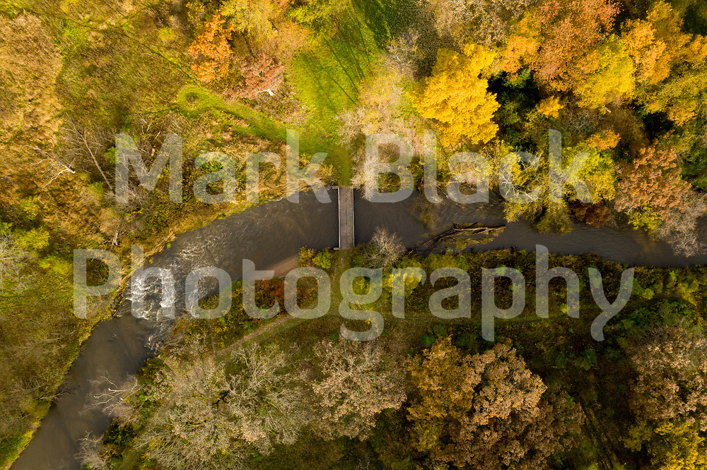 Ferson Creek flows under a foot bridge and through the tree showing off their autumn colors  as seen from above at LeRoy Oaks Forest Preserve in St. Charles, Illinois. Photo by Mark Black