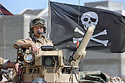 A British army soldier displays a Jolly Rogers pirate flag from his Ferret armoured scout car during the Persian Gulf War February 24, 1991 in Saudi Arabia.