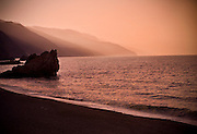 A large rock sits just off the shore in the waters off the coast of Italy at sunset