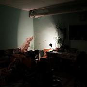 A single desk lamp illuminates a room of one of the many bomb shelters around Donetsk.