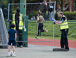 © Licensed to London News Pictures. 04/04/2020. London, UK. A young boy with a football watches fencing being erected around an area of at Paddington Recreation Ground in London to prevent people exercising in groups. The public have been told they can only leave their homes when absolutely essential, in an attempt to fight the spread of coronavirus COVID-19 disease. Photo credit: Ben Cawthra/LNP