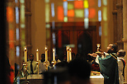 """Rev David Jones presents the Eucharist during the 33rd Annual African American Heritage Month Mass at Holy Name Cathedral. This year's mass celebrates the the Nguzo Saba principle of Kuumba, or """"creativity"""" at Holy Name Cathedral."""