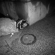 A homeless man sleeping by by a heated exhaust vent for an office tower on King Street West in Toronto's Financial District..(Credit Image: © Louie Palu/ZUMA Press)