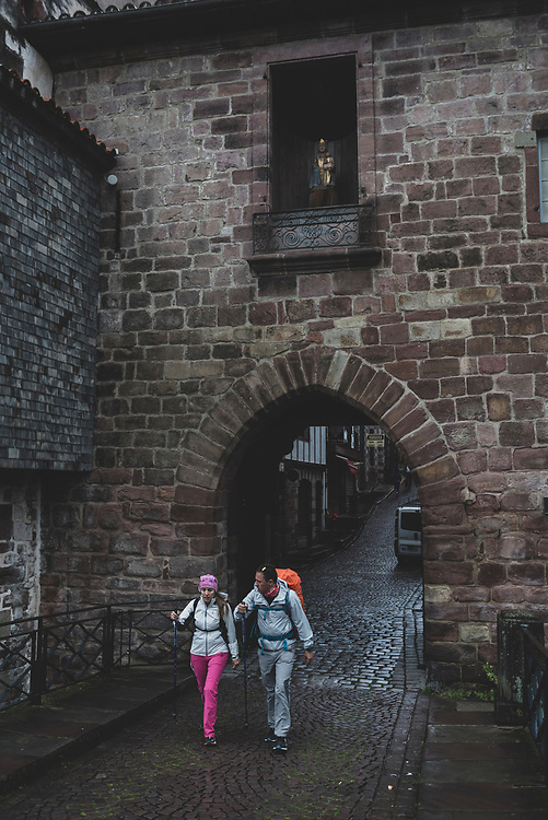 Two people pass through the Notre Dame Gate, beginning their journey on the Camino de Santiago, in Saint-Jean-Pied-de-Port, France. (May 28, 2018)<br /> <br /> DAY 1: SAINT-JEAN-PIED-DE-PORT TO RONCESVALLES -- 24 KM