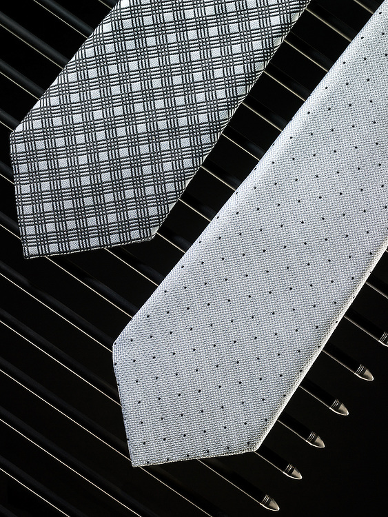 Two mens silk neckties draped over carbon arrows.