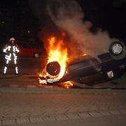 Autobrand Gemeenlandslaan Huizen, auto op de kop, brandweer blussen