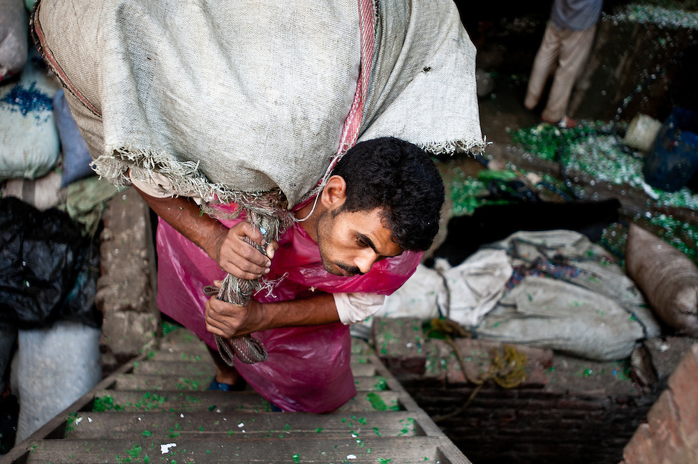 A man carries a heavy bag of washed plastic chips to the roof to dry.