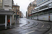Empty tram lines looking up Corporation Street with what is affectionately known the ramp on the right in Birmingham city centre, which is virtually deserted under Coronavirus lockdown on a wet rainy afternoon on 28th April 2020 in Birmingham, England, United Kingdom. Britains second city has been in a state of redevelopment for some years now, but with many outdated architectural remnants still remaining, on a grey day, the urban landscape appears as if frozen in time. Coronavirus or Covid-19 is a new respiratory illness that has not previously been seen in humans. While much or Europe has been placed into lockdown, the UK government has put in place more stringent rules as part of their long term strategy, and in particular social distancing.