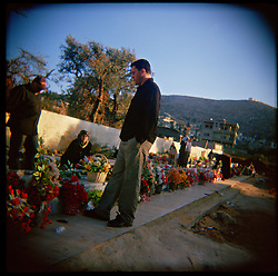 Hussein, Nadia and Hassan Al-Akhrass visit the grave of their family members who were killed in the war between Israel and Hezbollah, Aytaroun, Southern Lebanon, Oct. 23, 2006.
