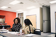 """SELMA, AL – DECEMBER 19, 2019: Keshee Dozier-Smith (left), 34, looks over documents at a YMCA Board of Directors meeting. Dozier-Smith took her seat on the Selma-Dallas County YMCA Board of Directors in September, 2019, and views her involvement there as an opportunity to encourage overall fitness and wellness within the community, and within the Rural Health Medical Program network. """"It's really part of our broader mission at Rural Health Medical Program – helping our patients connect with the community through health, fitness and wellness, and to bring people from different walks of life together.""""<br /> <br /> Since joining Rural Health Medical Program as Chief Executive Officer in March 2016, Dozier-Smith has effectively moderned the 35-year-old floundering business – opening three new clinics, streamlining processes and reaching out to local companies to offer healthcare services for employees. In the wake of rising hospital closures that leave Alabama's poorest citizens disproportionately cut off from access to medical care, Dozier-Smith represents a renewed effort to bridge the rural gap by offering a quality, affordable healthcare option."""