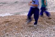 Children running on pebble beach, motion-blurred. Makarska, Croatia