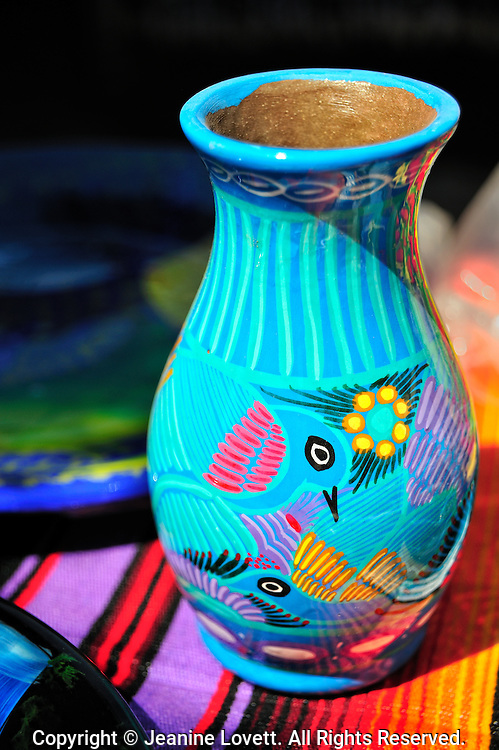 Vase painted with birds decoration on top of mexican rug.