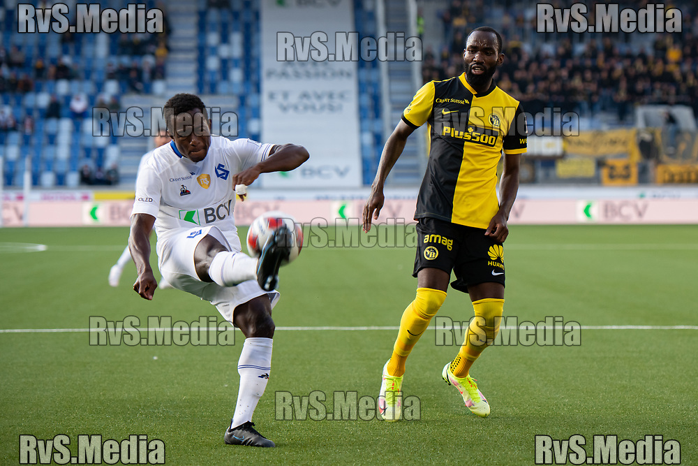 LAUSANNE, SWITZERLAND - SEPTEMBER 22: Armel Junior Zohouri #24 of FC Lausanne-Sport passes the ball in front of Nicolas Moumi Ngamaleu #13 of BSC Young Boys during the Swiss Super League match between FC Lausanne-Sport and BSC Young Boys at Stade de la Tuiliere on September 22, 2021 in Lausanne, Switzerland. (Photo by Basile Barbey/RvS.Media)