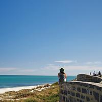 Sunsmart woman wearing a green hat looking over Cottesloe Main Beach