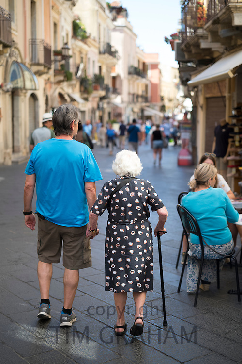 Two generations doing the passeggiata, strolling, in Corso Umberto I in the city of Taormina, East Sicily, Italy