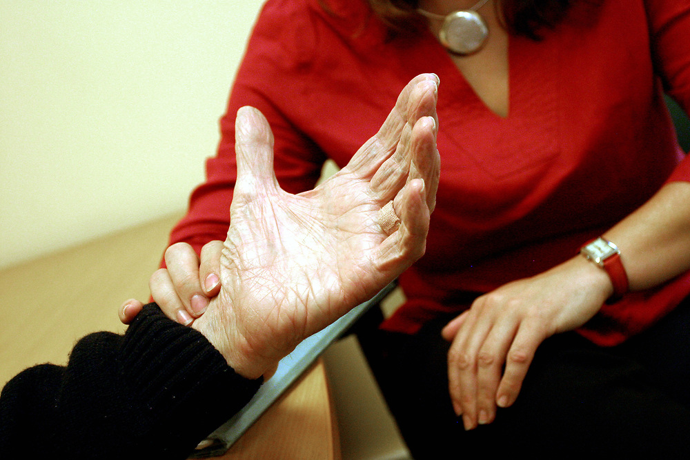 Nurse/Doctor taking patients pulse. Not recognisable. Hospice care, Orpington, UK