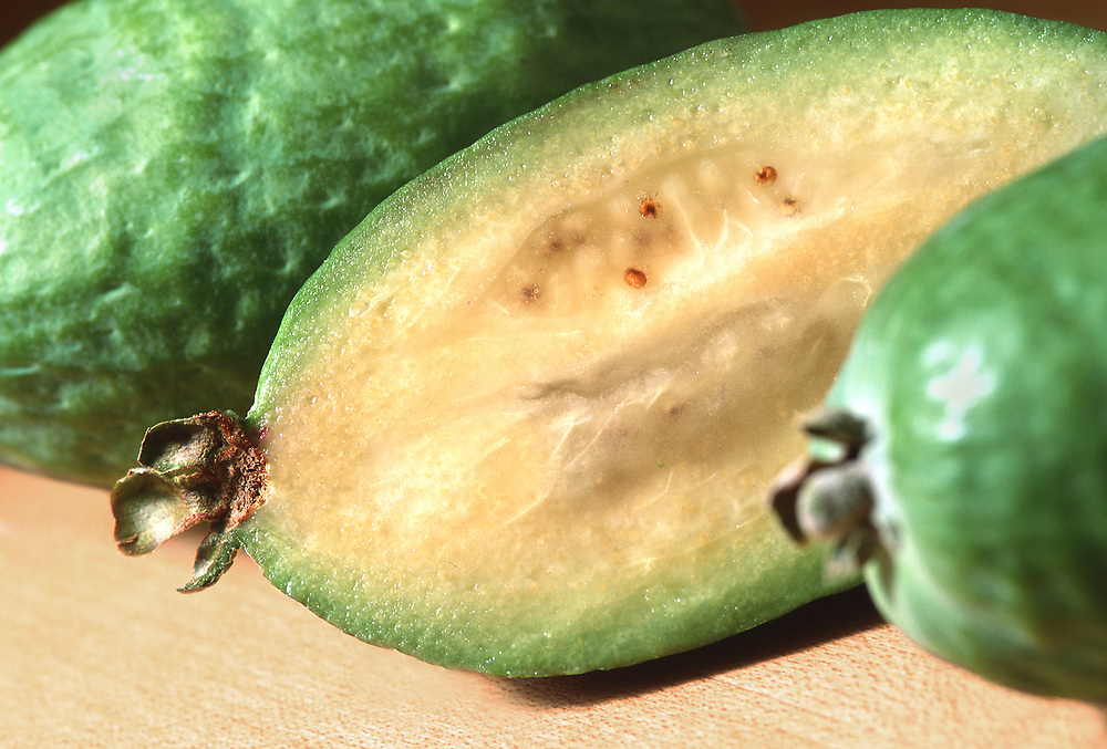 Close up selective focus photograph of three Feijoa on a butcher block counter with one cut open
