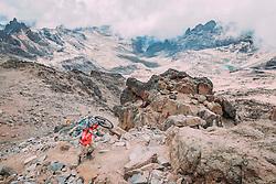 Swiss-American Hans Rey carries his bike on his back up to the peak of Mount Keya