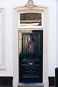 Quaint traditional wooden green front door entrance doorway in the town of Edam, The Netherlands