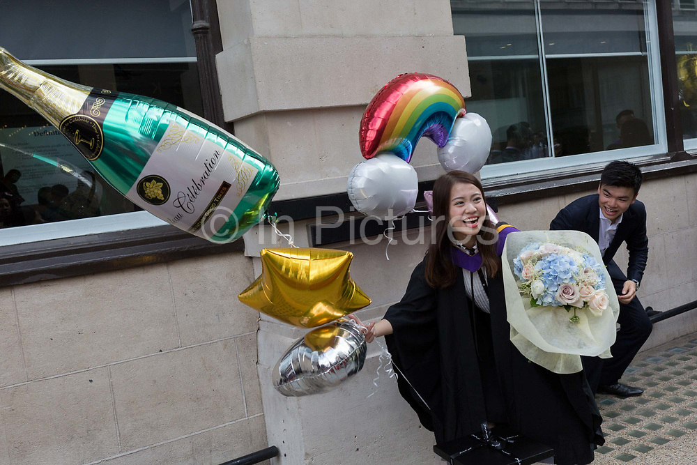 Hillary Chung, a 21 year-old Law graduate from Hong Kong, celebrates her graduation with a 2:1 degree outside the London School of Economics LSE after her graduation ceremony, on 22nd July 2019, in London, England.